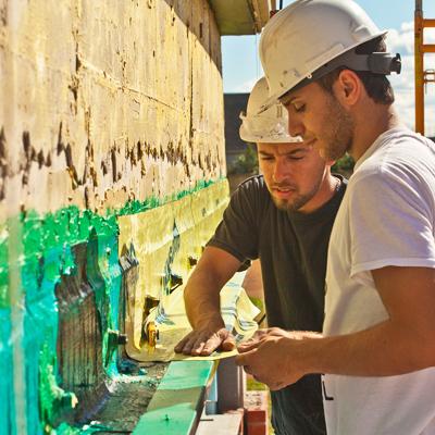 man wearing hard hat fixing wall